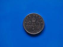 moneda de 5 peniques, Reino Unido sobre azul Imagen de archivo libre de regalías