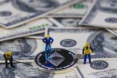 Moneda de plata de excavación del ethereum del trabajador miniatura de la gente en cientos billetes de dólar Explotación minera v Imágenes de archivo libres de regalías