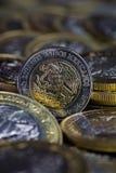 Moneda de un Peso mexicano entre más monedas Foto de archivo libre de regalías