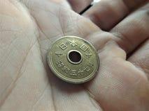 Moneda de 5 yenes japoneses en mi mano foto de archivo libre de regalías