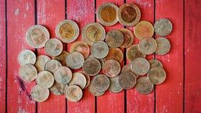 Moneda del baht de Rusty Thai en fondo de madera rojo imagenes de archivo
