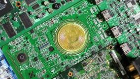 Moneda del bitcoin de la cámara lenta situada en placas de circuito del ordenador metrajes