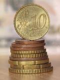 Moneda del centavo euro diez que equilibra en un top de la pila de las monedas. Imágenes de archivo libres de regalías