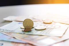 Moneda del centavo euro 50 en billetes de banco euro Fotografía de archivo