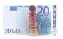 1 moneda del centavo que se coloca encima de la pila de monedas euro acerca al billete de banco del euro 20 Imagen de archivo