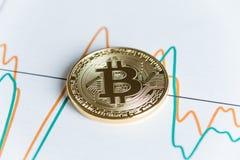 Moneda del cryptocurrency del bitcoin del oro en clavar la línea gráfico que negocia c Fotografía de archivo