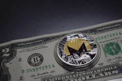 Moneda del cryptocurrency de Monero en dos dólares de billete de banco foto de archivo