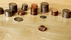 Moneda del dinero que gira y que hace girar en la tabla de madera en la cámara lenta Penique de giro metrajes