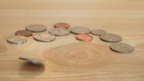 Moneda del dinero que gira y que hace girar en la tabla de madera Cuarto de giro metrajes