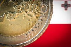 Moneda del euro 2 con una bandera borrosa de Malta en el fondo imagen de archivo