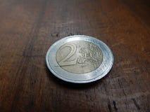 moneda del euro 2 en viejo fondo de madera de la tabla Imagen de archivo