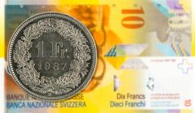 1 moneda del franco suizo contra anverso de la nota del franco suizo 10 fotografía de archivo libre de regalías