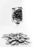 Moneda en copas de vino Imagen de archivo libre de regalías