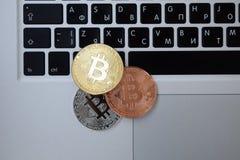 Moneda en el ordenador portátil del teclado, concepto electrónico del bitcoin de la moneda de oro de las finanzas Negocio, anunci imagenes de archivo