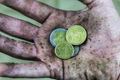 Moneda en los desamparados sucios de la mano Imágenes de archivo libres de regalías