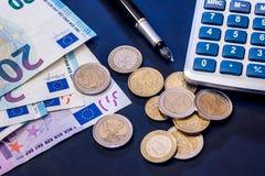 moneda euro con el billete de banco, la pluma y la calculadora Fotografía de archivo libre de regalías