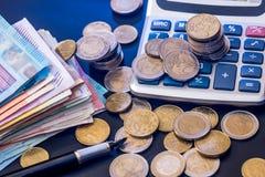 moneda euro con el billete de banco, la pluma y la calculadora aislados Foto de archivo