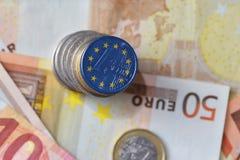 Moneda euro con la bandera de la unión europea en el fondo euro de los billetes de banco del dinero Fotos de archivo