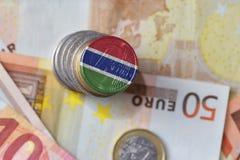 Moneda euro con la bandera nacional de Gambia en el fondo euro de los billetes de banco del dinero Imagen de archivo