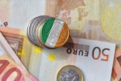 Moneda euro con la bandera nacional de Irlanda en el fondo euro de los billetes de banco del dinero Fotografía de archivo