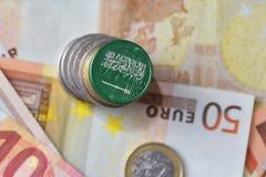 Moneda euro con la bandera nacional de la Arabia Saudita en el fondo euro de los billetes de banco del dinero Foto de archivo libre de regalías