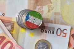 Moneda euro con la bandera nacional de la Guinea Ecuatorial en el fondo euro de los billetes de banco del dinero Imagenes de archivo