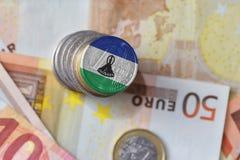 Moneda euro con la bandera nacional de Lesotho en el fondo euro de los billetes de banco del dinero Imágenes de archivo libres de regalías