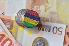 Moneda euro con la bandera nacional de Mauricio en el fondo euro de los billetes de banco del dinero Foto de archivo