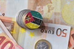 Moneda euro con la bandera nacional de Mozambique en el fondo euro de los billetes de banco del dinero Fotos de archivo