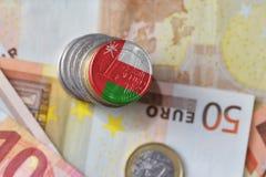 Moneda euro con la bandera nacional de Omán en el fondo euro de los billetes de banco del dinero Imagenes de archivo