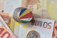 Moneda euro con la bandera nacional de Seychelles en el fondo euro de los billetes de banco del dinero Fotos de archivo libres de regalías