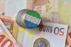 Moneda euro con la bandera nacional de Sierra Leona en el fondo euro de los billetes de banco del dinero Imagen de archivo