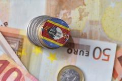 Moneda euro con la bandera nacional de Swazilandia en el fondo euro de los billetes de banco del dinero Imagen de archivo libre de regalías