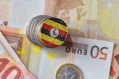 Moneda euro con la bandera nacional de Uganda en el fondo euro de los billetes de banco del dinero Imágenes de archivo libres de regalías