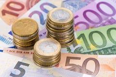 Moneda euro con los billetes de banco y las monedas Imagen de archivo libre de regalías