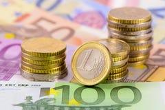 Moneda euro con los billetes de banco y las monedas Imágenes de archivo libres de regalías