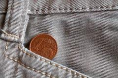 Moneda euro con una denominación de 1 centavo euro en el bolsillo de los vaqueros blancos del dril de algodón Imagen de archivo libre de regalías