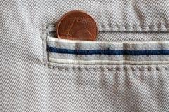 Moneda euro con una denominación de 1 centavo euro en el bolsillo de los vaqueros blancos del dril de algodón con la raya azul Fotografía de archivo libre de regalías
