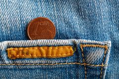 Moneda euro con una denominación de 1 centavo euro en el bolsillo de vaqueros azules llevados viejo vintage del dril de algodón Fotos de archivo libres de regalías