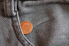 Moneda euro con una denominación de 1 centavo euro en el bolsillo de vaqueros marrones llevados viejos del dril de algodón Imágenes de archivo libres de regalías