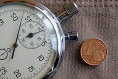 Moneda euro con una denominación de 1 centavo euro y cronómetro en el viejo contexto beige de los vaqueros - fondo del negocio Foto de archivo libre de regalías