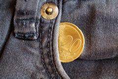 Moneda euro con una denominación de 20 centavos euro en el bolsillo de vaqueros azules obsoletos del dril de algodón Imágenes de archivo libres de regalías