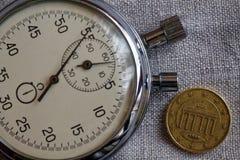 Moneda euro con una denominación de diez centavos euro y cronómetros en el contexto de lino blanco - fondo del negocio Imágenes de archivo libres de regalías