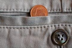 Moneda euro con una denominación de un centavo euro en el bolsillo de los vaqueros blancos del dril de algodón con el botón Imágenes de archivo libres de regalías