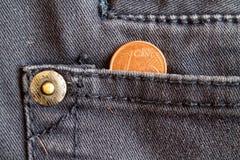 Moneda euro con una denominación de un centavo euro en el bolsillo de vaqueros azules gastados del dril de algodón Fotos de archivo