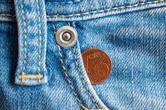 Moneda euro con una denominación de un centavo euro en el bolsillo de vaqueros azules llevados viejos del dril de algodón del vin Foto de archivo