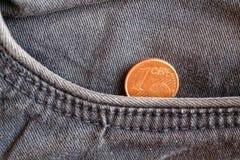 Moneda euro con una denominación de un centavo euro en el bolsillo de vaqueros azules viejos del dril de algodón Foto de archivo
