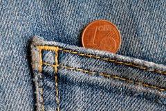 Moneda euro con una denominación de un centavo euro en el bolsillo de vaqueros azules viejos del dril de algodón Fotografía de archivo
