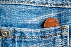 Moneda euro con una denominación de un centavo euro en el bolsillo de vaqueros azules viejos gastados del dril de algodón Fotos de archivo libres de regalías