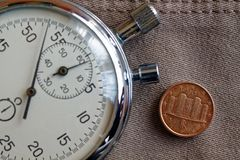 Moneda euro con una denominación de un centavo euro (lado trasero) y del cronómetro en el viejo contexto beige de los vaqueros -  Fotografía de archivo libre de regalías